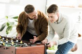 smiling father and teen son playing table football at home