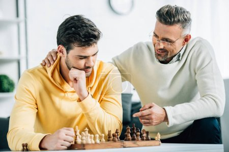 Photo for Son and mature father playing chess together on weekend at home - Royalty Free Image