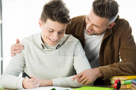 smiling father hugging cheerful teen son while he doing homework