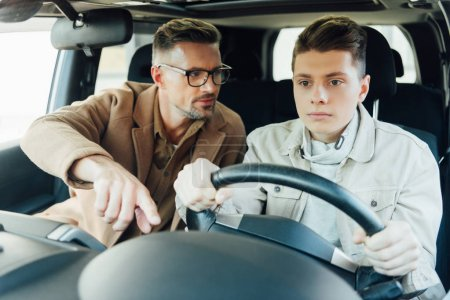 Photo for Handsome father teaching teen son driving car and pointing on something - Royalty Free Image