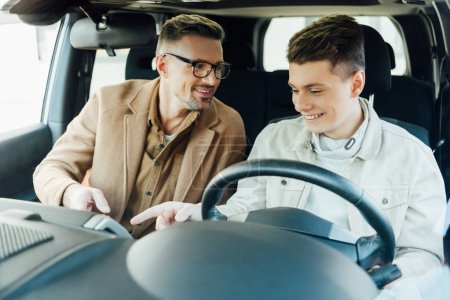 smiling handsome father teaching teen son driving car