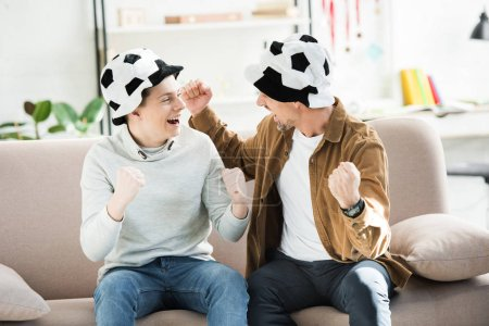 excited father and teen son in football hats watching game and screaming on sofa at home, looking at each other