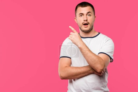 young man looking at camera while doing idea gesture isolated on pink