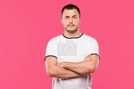 confident handsome young man posing with crossed arms isolated on pink