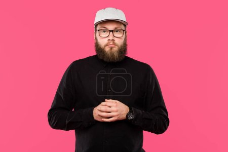serious bearded male hipster in cap hat and eyeglasses looking at camera isolated on pink