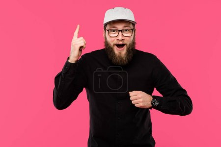 excited bearded man in eyeglasses and cap hat doing idea gesture isolated on pink
