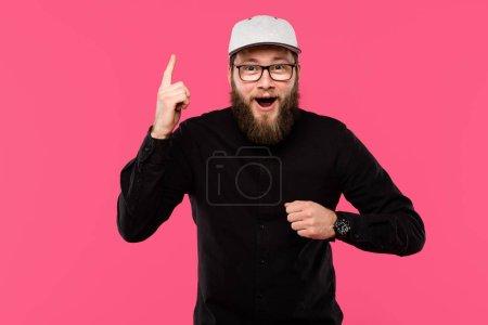 Photo pour Heureux homme barbu à lunettes et chapeau bouchon faire geste idée isolé sur rose - image libre de droit