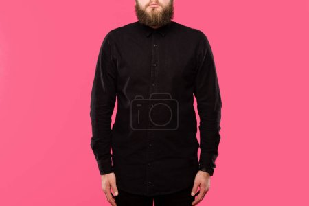 partial view of bearded male hipster in black stylish shirt posing isolated on pink