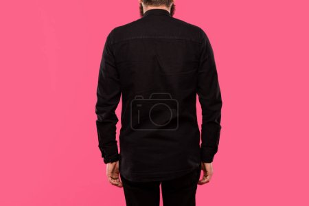 rear view of man in black stylish shirt posing isolated on pink