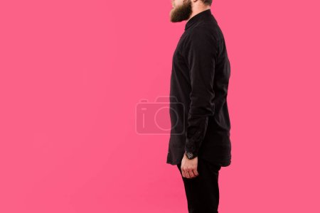 partial view of bearded man in black stylish shirt posing isolated on pink
