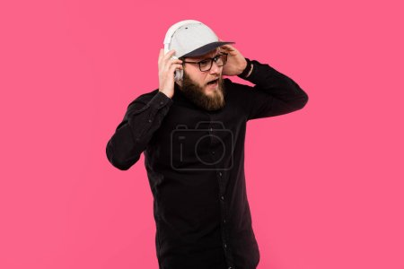 disappointed bearded male hipster taking off headphones isolated on pink