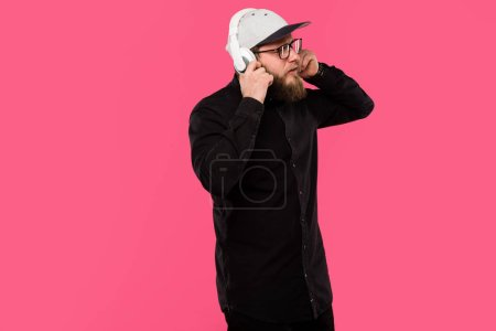 stylish bearded male hipster wearing eyeglasses and cap hat listening music in headphones isolated on pink