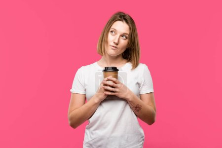 Photo for Dreamy girl holding disposable cup of coffee isolated on pink - Royalty Free Image