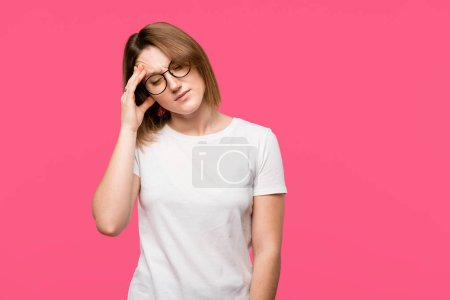 angry young woman in eyeglasses having headache isolated on pink