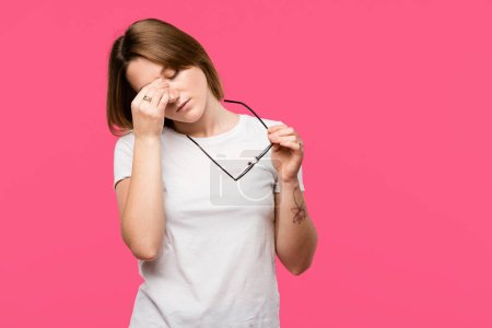 exhausted young woman holding eyeglasses while having headache isolated on pink