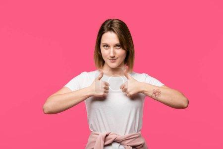 Photo pour Souriant tatoué fille montrant pouces jusqu'à geste isolé sur rose - image libre de droit