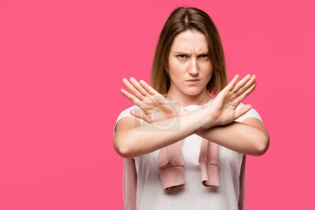 Photo for Angry young woman showing stop gesture with crossed arms isolated on pink - Royalty Free Image