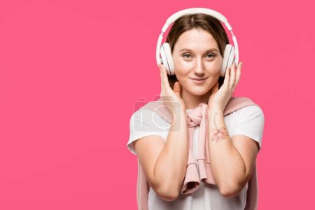 Photo for Happy young woman in headphones listening music isolated on pink - Royalty Free Image
