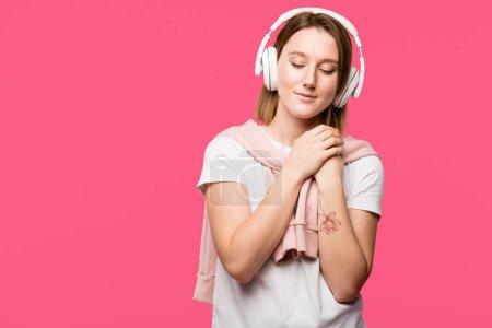 joyful young woman in headphones listening music isolated on pink