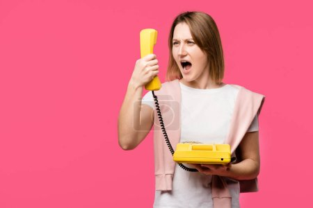 angry young woman yelling at handset isolated on pink