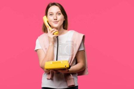 beautiful young woman talking by rotary phone and smiling at camera isolated on pink