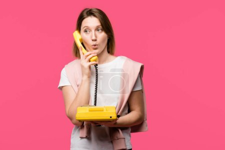 surprised young woman talking by rotary phone isolated on pink
