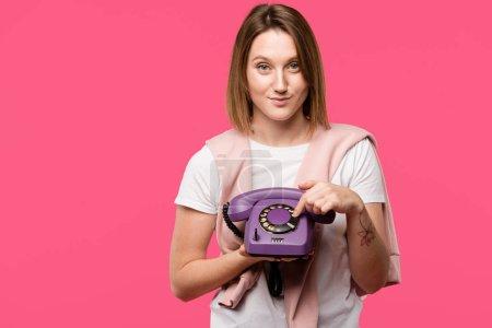 Foto de Hermosa joven sosteniendo teléfono rotatorio y sonriendo a cámara aislada en rosa - Imagen libre de derechos