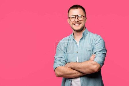 handsome happy man standing with crossed arms and smiling at camera isolated on pink