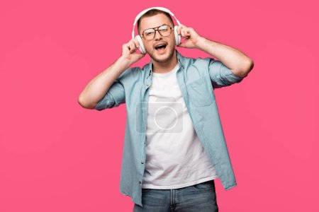 happy young man in eyeglasses listening music in headphones and smiling at camera isolated on pink