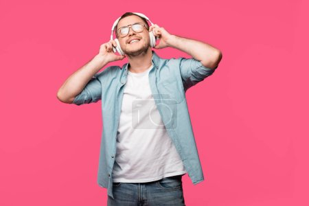 happy young man in eyeglasses listening music in headphones isolated on pink