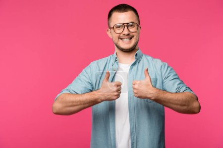 Photo for Cheerful young man in eyeglasses showing thumbs up and smiling at camera isolated on pink - Royalty Free Image