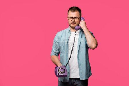 Photo pour Fronçant les sourcils jeune homme parler par téléphone vintage et regardant la caméra isolée sur rose - image libre de droit