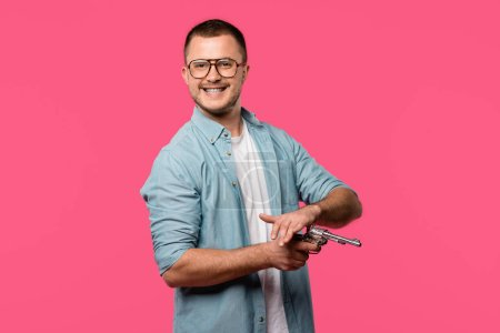 young man in eyeglasses holding revolver and smiling at camera isolated on pink