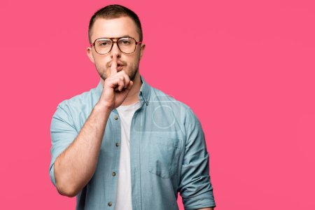 young man gesturing for silence with finger on lips and looking at camera isolated on pink