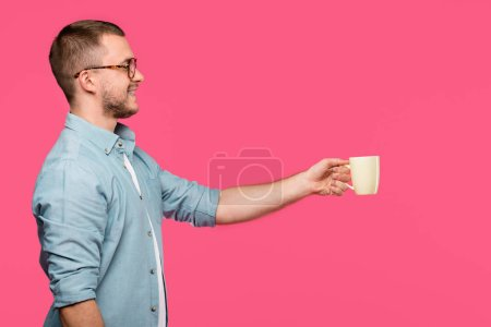 side view of smiling man holding mug and looking away isolated on pink