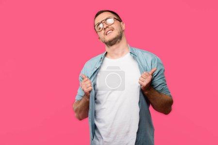 Foto de Hombre joven fresco en anteojos sosteniendo la camiseta y mostrando los pulgares para arriba de color rosa aislada en - Imagen libre de derechos