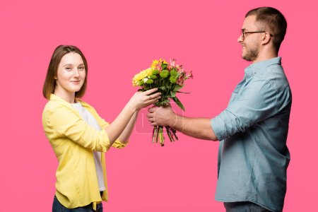 happy young man presenting bouquet of flowers to smiling woman isolated on pink