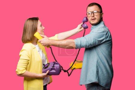 Foto de Vista lateral de la joven pareja manteniendo rotatorios teléfonos y uno para el otro aislado en rosa - Imagen libre de derechos