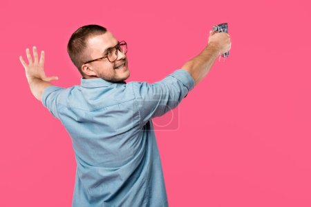 back view of smiling man in eyeglasses holding staple gun and looking at camera isolated on pink