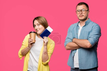 Photo for Man in eyeglasses standing with crossed arms and looking at camera while smiling woman holding passport, boarding pass and coffee to go isolated on pink - Royalty Free Image