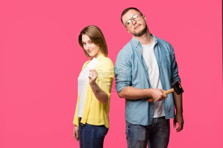young couple with hammer and blank card looking at camera isolated on pink
