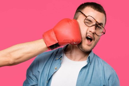 Photo for Cropped shot of someone in boxing glove hitting man in eyeglasses isolated on pink - Royalty Free Image