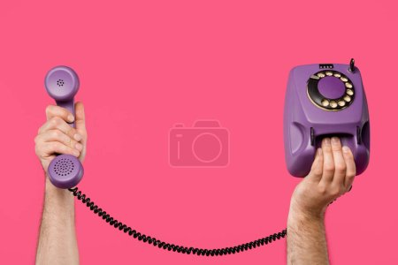 cropped shot of man holding purple rotary phone isolated on pink