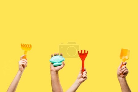 cropped shot of male and female hands holding colorful plastic toys isolated on yellow