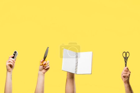 cropped shot of male and female hands holding scissors, stapler and blank notepad isolated on yellow