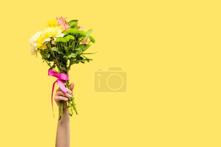 cropped shot of person holding beautiful bouquet of flowers isolated on yellow
