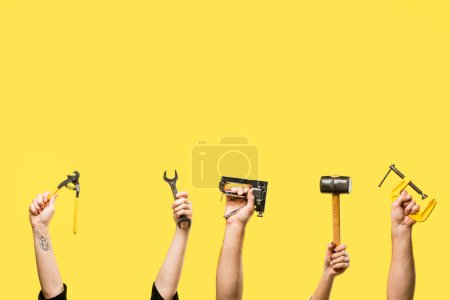 Cropped shot of hands holding staple gun, wrench, handheld, hammer isolated on yellow