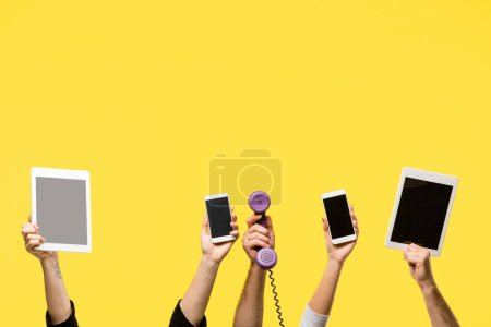 cropped shot of hands holding smartphones, digital tablets and handset isolated on yellow