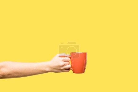 Photo pour Plan recadré de la personne tenant la tasse rouge isolé sur jaune - image libre de droit