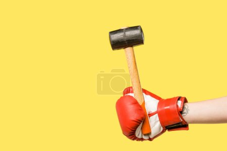 Photo for Cropped shot of person in boxing glove holding hammer isolated on yellow - Royalty Free Image